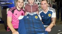 Young Scotland fan Christopher Lithgow gets a autograph from Scotland U21 Paterson (left) and Brown